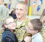 A Soldier with Task Force Saber, 1st Combat Aviation Brigade, 1st Infantry Division, hugs his children following a Nov. 17 redeployment ceremony at Marshall Army Airfield.  The task force was deployed to Afghanistan in support of Operation Enduring Freedom.  Photo by: Sgt. Keven Parry, 1ST CAB.