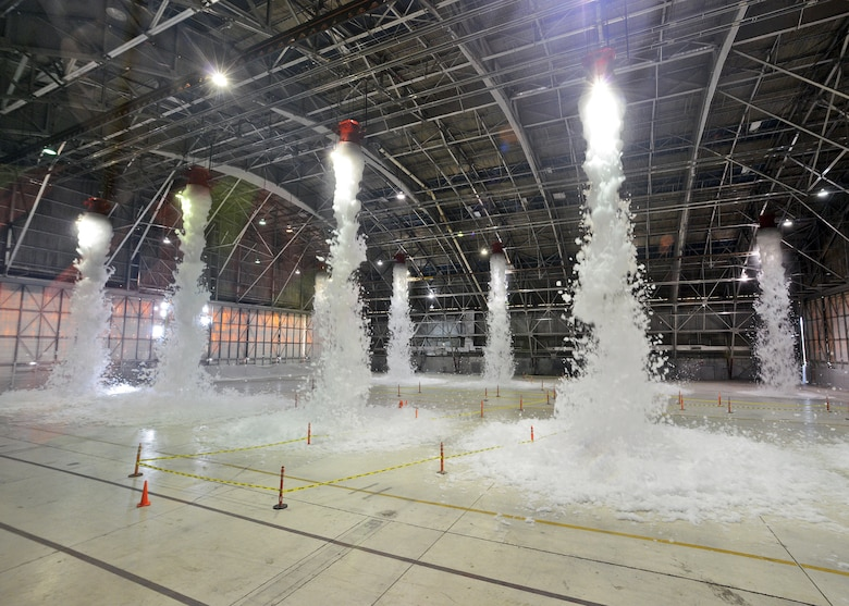 The interior of Hangar 1210 was the site of the base's most recent emergency scenario exercise that occurred Nov. 26. The hangar, which has 10 large capacity and 2 small capacity foam generators, released approximately 110 gallons of two percent Ansul Jet-Ex foam concentrate that is part of the newly-installed fire suppression system. The foam is detergent-based with additives to keep it stable and keep it from freezing. The purpose of the exercise was so Exercise Evaluation Team members could assess how on-base emergency response personnel gain and maintain control of a site after a fire suppression system discharge incident has occurred. (U.S. Air Force photo by Jet Fabara)