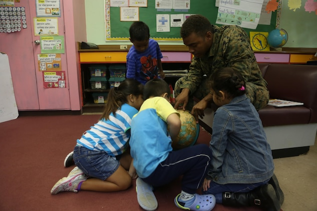 Lance Cpl. Sterling L. Meriweather helps children at Tinian Elementary School find Tinian on a globe during a community relations event Dec. 4. The servicemembers are here participating in Exercise Forager Fury II. FF II is an aviation training relocation event intended to meet U.S.-Japan bilateral goals such as reduced local impacts by dispersing the training to other areas and increased operational readiness.  The service members volunteered time to spend time with the children. Meriweather is a satellite communications specialist with Marine Air Control Group 18, 1st Marine Aircraft Wing, III Marine Expeditionary Force.