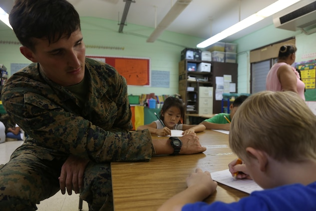 Lance Cpl. Michael Bridenstine helps a group of first graders with their writing skills at Tinian Elementary School during a community relations event Dec. 4. The servicemembers are on Tinian as part of Exercise Forager Fury II. The purpose of FF II is to employ and assess combat power generation and operations in a deployed, austere and unimproved environment.  The service members volunteered time out of their daily routine to spend time with the children, interact and play games. Bridenstine is a chemical biological radiological nuclear defense specialist with Marine Wing Support Squadron 171, Marine Aircraft Group 12, 1st Marine Aircraft Wing, III Marine Expeditionary Force.