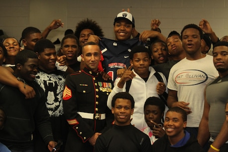 Orlando Brown Jr. poses with his teammates and Sgt. Luis R. Crovetto during a jersey presentation at Peachtree Ridge High School in Suwanee, GA, Nov. 20. The presentation spotlighted Brown as one of 90 high school student athletes selected to play in the Semper Fidelis All-American Bowl on Jan. 5, 2014 in Carson, Calif. The Semper Fidelis All-American Bowl demonstrates the Marine Corps' commitment to developing quality citizens and reinforces core values of honor, courage, and commitment. The Semper Fidelis All-American Bowl offers an opportunity for quality players, coaches and Marines to meet, practice and work together to teach skills important on and off the field, such as leadership, self-confidence and teamwork. The game airs on Jan. 5, 2014 at 9 p.m. Eastern Standard Time live on Fox Sports 1. Crovetto is a recruiting at United States Marine Corps Recruiting Sub-Station Buford, Recruiting Station Atlanta. (U.S. Marine Corps photo by Cpl. Courtney G. White/Released)