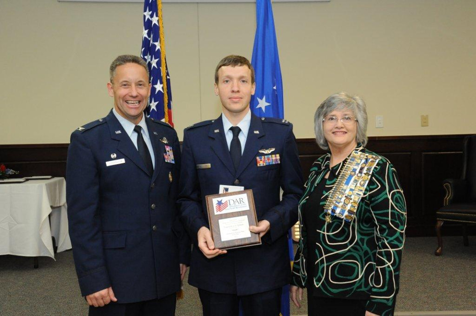 Col. Gerald Goodfellow (left), 12th Flying Training Wing commander, Joint Base San Antonio-Randolph, and Susan Green Tillman (center right), State Recording Secretary of Texas, Daughters of the American Revolution, present Capt. Brian Thalhofer with the Instructor Pilot of the Year Award. (U.S. Air Force photo by Rich McFadden)