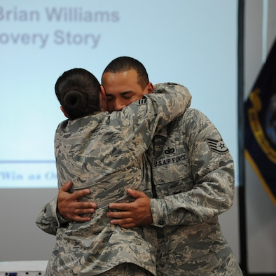 Staff Sgt. Brian Williams hugs his fiancée, Staff Sgt. Emily Christofaro, after finding out he received a promotion to technical sergeant Oct. 30, 2013, at the New Jersey National Guard Armory in Bordentown, N.J. Williams returned to duty after recovering from an improvised explosive device attack while deployed to Afghanistan. Williams is a 87th Security Forces Squadron military working dog handler. (U.S. Air Force photo by 1st Lt. Alexis McGee/Released)