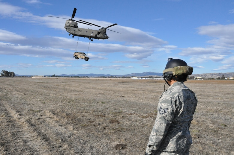 Staff Sgt. Ryan Torralba watches a CH-47 Chinook as it carries a Humvee with a cargo sling Nov. 21, 2013, on Travis Air Force Base. Calif. Torralba is assigned 60th Aerial Port Squadron aerial porter. (U.S. Air Force photo/Staff Sgt. Patrick Harrower)