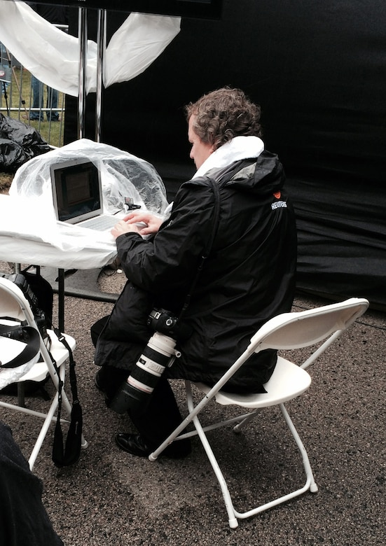 A reporter files his story on a laptop draped with plastic sheeting on the bitterly cold and damp 50th anniversary ceremony to remember President John F. Kennedy in Dallas.