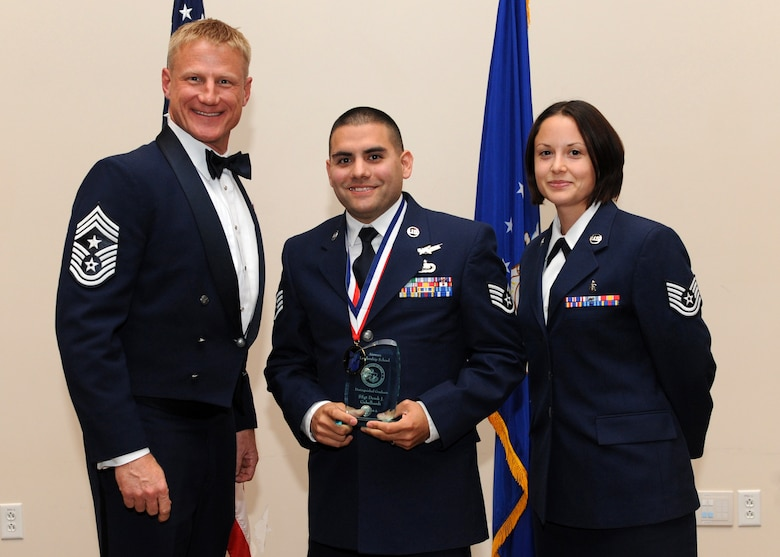Staff Sgt. Derek J. Gebelhardt, 566th Intelligence Squadron, center, receives the Distinguished Graduate Award during the Buckley Airman Leadership School Class 14-A graduation Dec. 4, 2013, at the Leadership Development Center on Buckley Air Force Base, Colo. The Distinguished Graduate Award is presented to the person with the second highest overall average in all graded areas who demonstrated a high level of leadership skills during ALS. (U.S. Air Force photo by Senior Airman Marcy Copeland/Released)