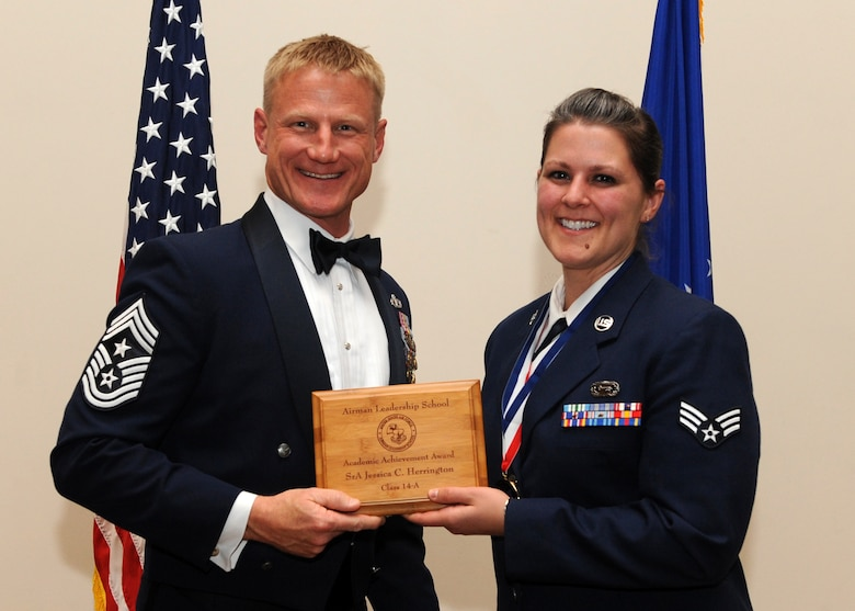Chief Master Sgt. Craig Hall, 460th Space Wing command chief, presents Senior Airman Jessica C. Herrington, 566th Intelligence Squadron, right, the Academic Achievement Award during the Buckley Airman Leadership School Class 14-A graduation Dec. 4, 2013, at the Leadership Development Center on Buckley Air Force Base, Colo. The Academic Award is given to the student with the highest overall average score on all academic evaluations during ALS. (U.S. Air Force photo by Senior Airman Marcy Copeland/Released)