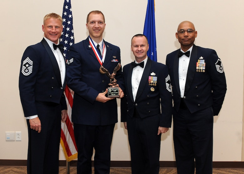 Senior Airman Vaughn A. Lauritzen, 460th Space Communications Squadron, second from left, receives the John L. Levitow Award during the Buckley Airman Leadership School Class 14-A graduation Dec. 4, 2013, at the Leadership Development Center on Buckley Air Force Base, Colo. The Levitow Award is presented to the student who demonstrated the most outstanding leadership and scholastic qualities. (U.S. Air Force photo by Senior Airman Marcy Copeland/Released)