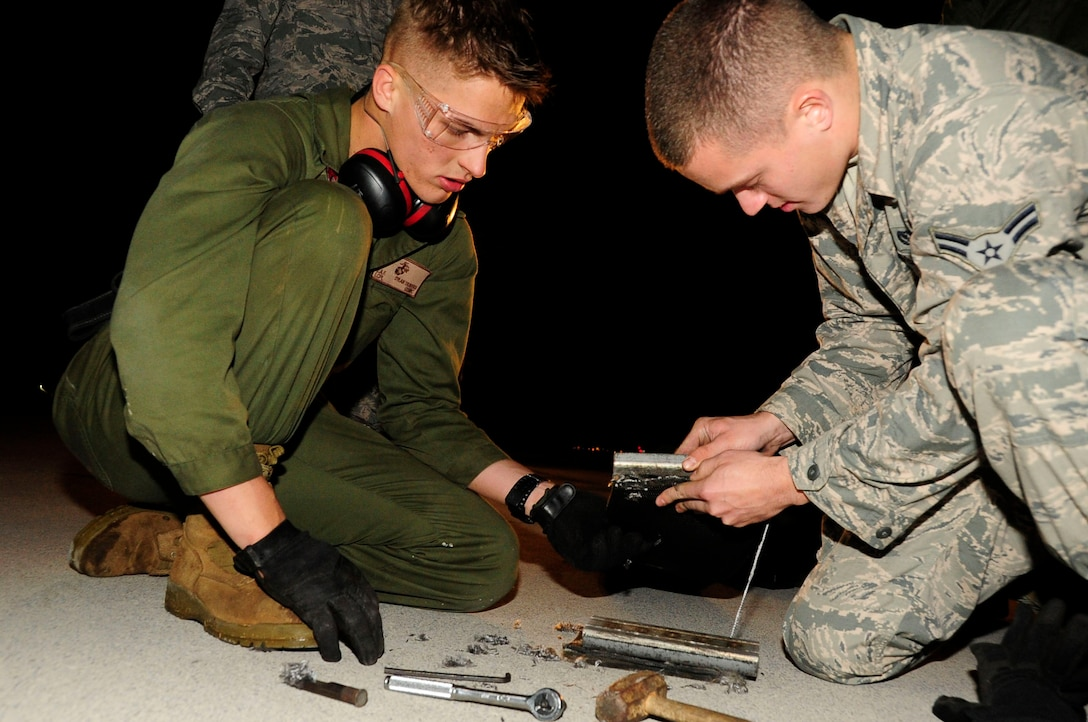 U.S. Marine Corps  Lance Cpl. Dylan Travers works with Airman 1st Class Justin Clifford to ensure the tape is secured tightly to the aircraft arresting tape connector on Kadena Air Base, Japan, Dec. 6, 2013. Barrier maintenance technicians punch holes into the tape so the tape connector can connect onto it. Travers is assigned to the Marine Wing Headquarters Squadron as an expeditionary airfield technician from Northfork, Calif. Clifford from Wash., is assigned to the 18th Civil Engineer Squadron electrical power production technician. (U.S. Air Force photo by Staff Sgt. Darnell T. Cannady)