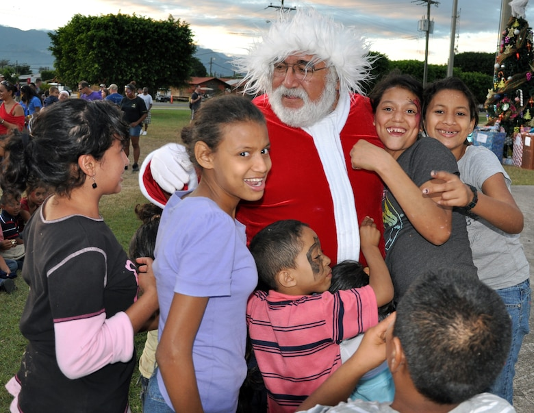 """Honduran orphans greet Santa Claus during Joint Task Force-Bravo's """"Operation Holiday Blessing,"""" at Soto Cano Air Base, Honduras, Dec. 6, 2013.  More than 300 Honduran orphans were treated to a day of activities, gifts, and holiday joy, provided by more than 200 volunteers from the Task Force.  (U.S. Air Force photo by Capt. Zach Anderson)"""