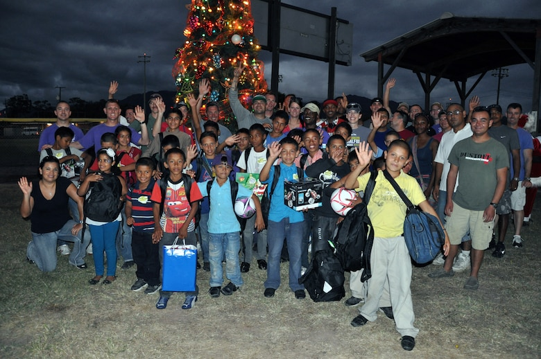 """Honduran orphans and members of Joint Task Force-Bravo pose in front of the tree during Joint Task Force-Bravo's """"Operation Holiday Blessing,"""" at Soto Cano Air Base, Honduras, Dec. 6, 2013.  More than 300 Honduran orphans were treated to a day of activities, gifts, and holiday joy, provided by more than 200 volunteers from the Task Force.  (U.S. Air Force photo by Capt. Zach Anderson)"""
