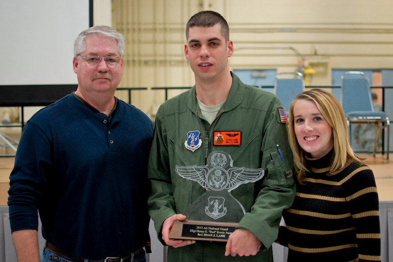 """U.S. Air Force Senior Airman Ryan J. Lane of the 169th Airlift Squadron, center, displays the Red Erwin award with family members at the 182nd Airlift Wing, Peoria, Ill., Dec. 8, 2013. Lane competed against 3,000 other Air National Guard candidates to win the Staff Sgt. Henry E. """"Red"""" Erwin Outstanding Enlisted Aircrew Member Airman of the Year Award. He was presented the honor for his outstanding accomplishments, leadership traits that impacted his unit's mission and self-improvement in areas such as education and training. (U.S. Air National Guard photo by Staff Sgt. Lealan C. Buehrer/Released)"""