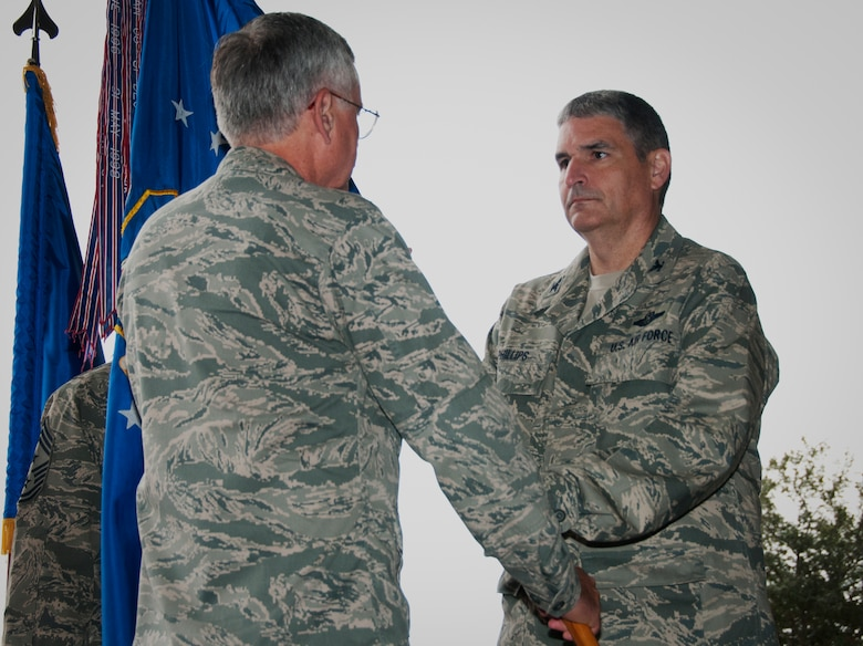 Col. James M. Phillips receives the wing guidon from Maj. Gen. George F. Williams, Air Force Special Operations Command mobilization assistant to the commander, during an assumption of command ceremony that installed him as commander of the 919th Special Operations Wing Dec.  7,  at Duke Field, Fla. (U.S. Air Force photo/Tech. Sgt. Jasmin Taylor)