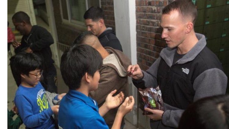 A service member passes out candy to a child from an orphanage in Gunsan during a community relations event, Nov. 5, 2013. Children of the orphanage were excited and tried to get service members to pass out candy before scheduled.