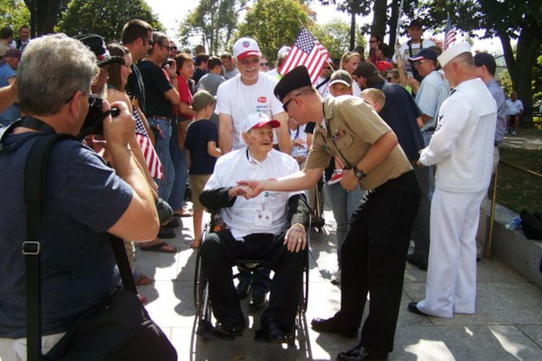 A Marine thanks Charles Gray for his military service as he heads to the World War II Memorial.