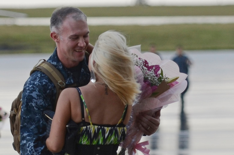 U.S. Navy Chief Petty Officer Gerold Bright, Helicopter Sea Combat Squadron 25 Detachment 6 maintenance chief, embraces his wife during the HSC-25 Det. 6 homecoming Dec. 9, 2013, on Andersen Air Force Base, Guam. During the unit's nine-month deployment aboard USS Bonhomme Richard, Det. 6 supported the U.S. Navy 7th Fleet in the Western Pacific area of responsibility. (U.S. Air Force photo by Senior Airman Marianique Santos/Released)