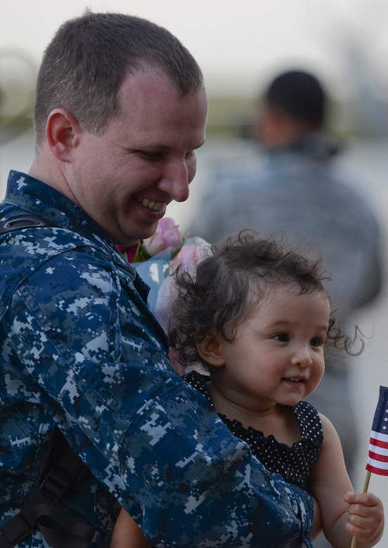 U.S. Navy Petty Officer 1st Class Thomas Ridgway, Helicopter Sea Combat Squadron 25 Detachment 6 aircraft electronics technician, holds his daughter during the HSC-25 Det. 6 homecoming Dec. 9, 2013, on Andersen Air Force Base, Guam. During the unit's nine-month deployment aboard USS Bonhomme Richard, Det. 6 supported the U.S. Navy 7th Fleet in the Western Pacific area of responsibility. (U.S. Air Force photo by Senior Airman Marianique Santos/Released)