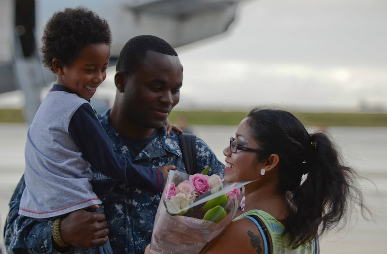 U.S. Navy Petty Officer 2nd Class Jerome Acquajameson, Helicopter Sea Combat Squadron 25 Detachment 6 aviation ordnanceman, embraces his family during the HSC-25 Det. 6 homecoming Dec. 9, 2013, on Andersen Air Force Base, Guam. During the unit's nine-month deployment aboard USS Bonhomme Richard, Det. 6 supported the U.S. Navy 7th Fleet in the Western Pacific area of responsibility. (U.S. Air Force photo by Senior Airman Marianique Santos/Released)