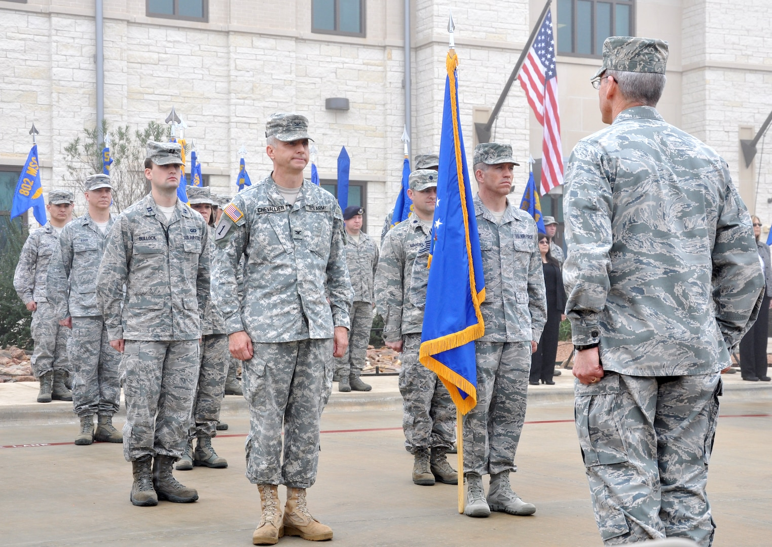 (From right) Brig. Gen. Bob LaBrutta, Joint Base San Antonio and 502nd Air Base Wing commander, receives the wing's colors from Chief Master Sgt. Alexander Perry,  JBSA/502nd ABW command chief master sergeant; and Army Col. Jim Chevallier, JBSA/502nd ABW vice commander during the 502nd Air Base Wing transformation ceremony at Joint Base San Antonio-Fort Sam Houston Dec. 4. (U.S. Air Force photo by Steve Elliott)