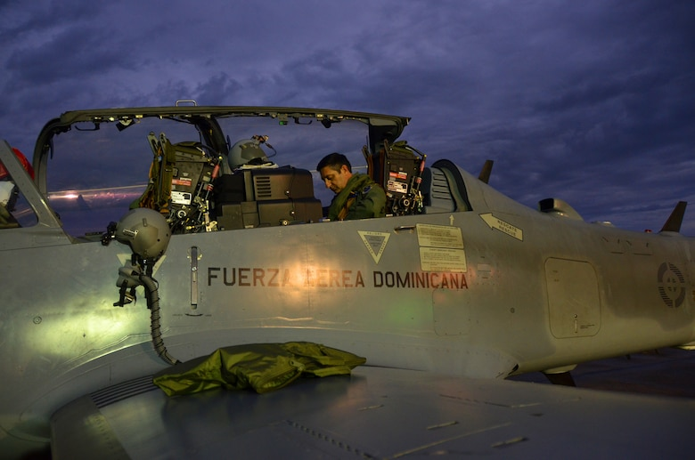 Col. Mike Torrealday, a U.S. Air Force F-16 instructor pilot, prepares for a nighttime flight in the back seat of a Dominican Republic air force A-29 Super Tucano as part of an exercise to combat illegal drug trafficking Dec. 4, 2013. The exercise is part of the Sovereign Skies Program, an initiative between the U.S., Colombian, and Dominican Republic air forces to share best-practices on procedures to detect, track and intercept illegal drugs moving north from South America. Since the program's inception, the number of aircraft suspected to traffic drugs through the Dominican Republic dropped from more than 100 annually to nearly zero. (U.S. Air Force photo by Capt. Justin Brockhoff/Released)