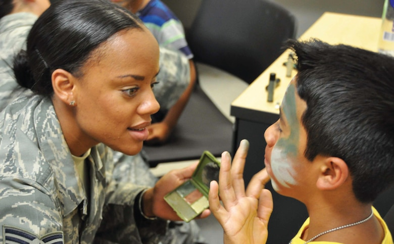 Staff Sergeant Shamera Coleman, 452nd Logistics Readiness Squadron, applies finishing touches to the camo-paint on 10-year-old Cristian Medina's face during a mock, deployment line set up by members of the squadron. Medina was among approximately 40 children, along with their parents, that attended the first Operation Family First event put on by the squadron, with support from the 452nd Security Forces Squadron and Medical Group, the Yellow Ribbon Program, USO, and others. (U.S. Air Force photo/Staff Sgt. Joe Davidson)