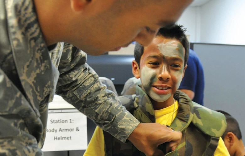 Senior Airman Jonathan Villa Vargas, 452nd Logistics Readiness Squadron, fits 10-year-old Cristian Medina, with Individual Body Armor during a mock deployment line set up for kids at the first-ever Operation Family First event held in Building 385, July 13. Medina was one of about 40 kids who participated along with parents and other relatives. The event was designed to give children a feel for what their deploying parents go through during a real-world deployment. (U.S. Air Force photo/Staff Sgt. Joe Davidson)