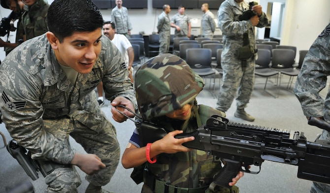 Senior Airman Andrew Reynoso, 452nd Security Forces Squadron, helps six-year-old Giovanni Medina get a clear sight picture as he holds on tight to the M240-Bravo Machine Gun. This, as well as other weapons, was on display during the Logistics Readiness Squadron's Operation Family First event held in Building 385, July 13. (U.S. Air Force photo/Staff Sgt. Joe Davidson)