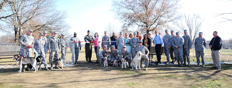 U.S. Air Force Brig. Gen. Thomas Bussiere, 509th Bomb Wing commander, and Mandy Barker, wife of Airman 1st Class Alex Barker from the 509th Civil Engineer Squadron, celebrate the ribbon-cutting for the new Whiteman Dog Park Dec. 3, 2013, at Whiteman Air Force Base, Mo. The park is open from dusk till dawn. (U.S. Air Force photo by Staff Sgt. Brigitte N. Brantley/Released)