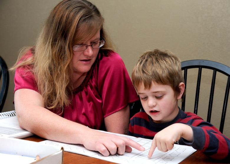 Amie Smithley works with her son Matthew on a lesson about the days of the week. Amie and her husband, Chaplain (Capt.) Jon Smithley, currently stationed at Vance Air Force Base, Okla., decided to home-school their five children. (U.S. Air Force photo/ Senior Airman Frank Casciotta)