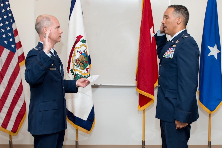 Col. Shaun Perkowski, 167th Airlift Wing commander, administers the oath of office to Col. David V. Cochran, wing vice commander, during Cochran's promotion ceremony, Nov. 15 at the 167th Airlift Wing. Both colonels began their careers in 1985 at the United States Air Force Academy. (Air National Guard photo by Master Sgt. Emily Beightol-Deyerle)