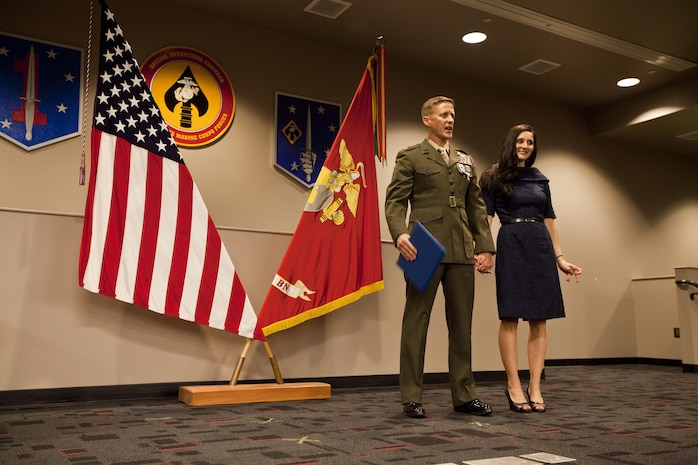 Maj. Robb McDonald, air officer with the 1st Marine Special Operations Battalion, from Yuma, Ariz., honors his wife, Jennifer, after receiving the Silver Star for his efforts against an enemy attack aboard Camp Bastion, Afghanistan in 2012. Lt. Gen. John A. Toolan, commanding general of I Marine Expeditionary Force pinned the nation's third highest award on McDonald aboard Camp Pendleton, Calif., Dec. 9.