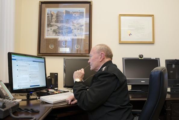 18th Chairman of the Joint Chiefs of Staff Gen. Martin E. Dempsey sits at his desk in the Pentagon and reads questions posted to his Facebook page during a Facebook Town Hall he hosted Dec. 5, 2013. This was the Chairman's first town hall utilizing social media as another way to receive feedback from the Joint Force.
