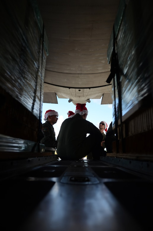 Members of a C-130 Hercules aircrew from Yokota Air Base, Japan, meet at the back of the aircraft to discuss flight plans before an Operation Christmas Drop flight Dec. 11, 2013, on Andersen Air Force Base, Guam. This year marks the 62nd year of Operation Christmas Drop, which began in 1952, making it the world's longest running airdrop mission. (U.S. Air Force photo by Senior Airman Marianique Santos/Released)