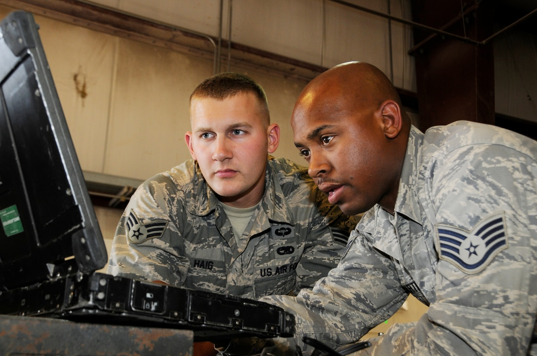 Senior Airman Michael Haig and Staff Sgt. Cornell Martin review a technical order before rewiring a generator at the 379th Air Expeditionary Wing in Southwest Asia, Dec. 9, 2013. Haig a Constableville, N.Y. native and Martin an El Paso, Texas, native, are 379th Expeditionary Maintenance Squadron Aerospace Ground Equipment specialists deployed from Dyess, Air Force Base, Texas. (U.S. Air Force photo/Senior Airman Hannah Landeros)