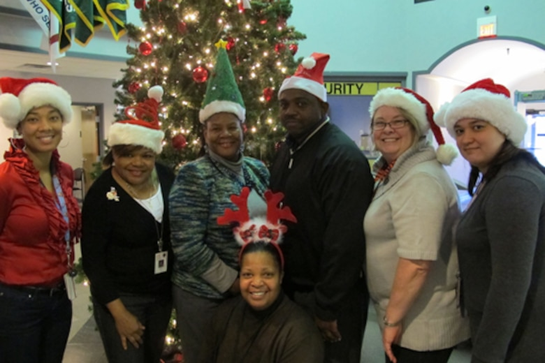 "Members of Huntsville Center's Installation Support and Programs Management Directorate's Facilities Division wear festive holiday hats during Christmas Hat Day Dec. 10 at Huntsville Center. The team is celebrating ""The 12 Days of Christmas"" at the Huntsville Center Dec. 9-20 to reduce stress in the workplace this holiday season."