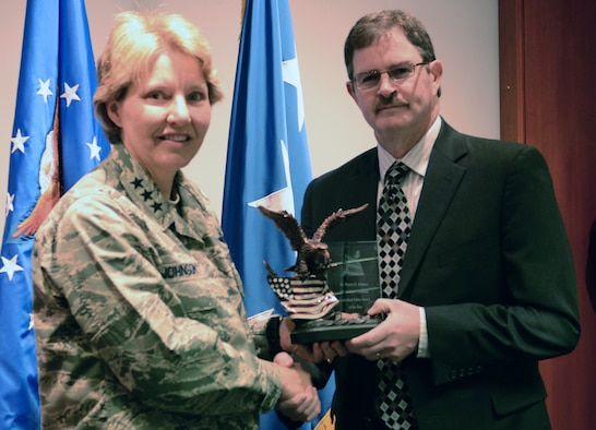 Academy Superintendent Lt. Gen. Michelle Johnson (left) presents an award to Martin Johnson, an electronics engineer from the Dean of Faculty, who was was named Safety Individual of the Year at the Academy Dec. 11 during an awards presentation. The Annual Safety Awards recognize outstanding individuals, units and groups for their contribution to the USAFA Safety program. (U.S. Air Force Photo/Senior Airman Veronica Ward)