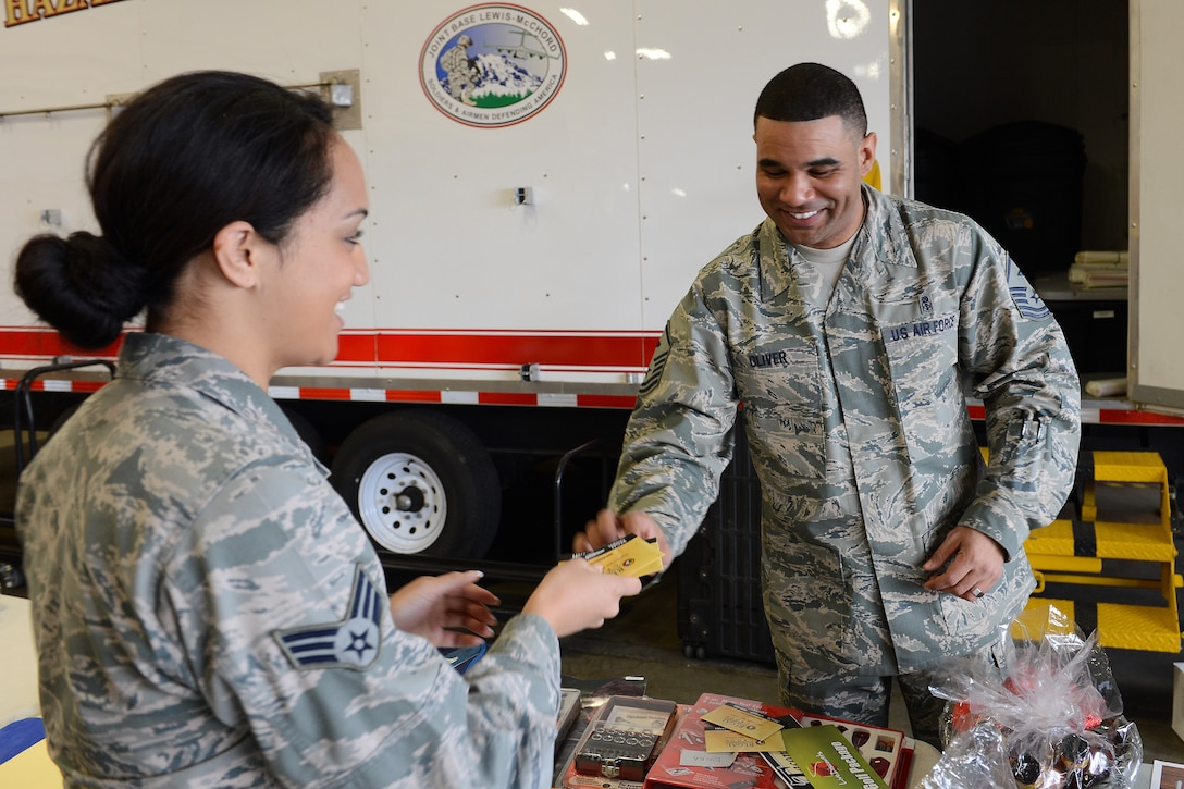 Master Sgt. Calvin Oliver, 10th Airlift Squadron first sergeant, gives out two free movie tickets to Senior Airman Pogisa Faumuina, Western Air Defense Sector military personnel technician, at the Airmen's Feast Dec. 11, 2013 at Joint Base Lewis-McChord, Wash. During the event Airmen received a free lunch and a variety of raffle prizes. (U.S. Air Force photo/Airman 1st Class Jacob Jimenez)
