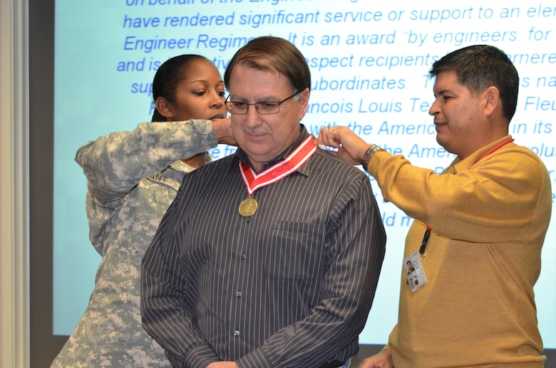 """ALBUQUERQUE, N.M., -- Lt. Col. Antoinette Gant and Chief of Engineering and Construction John Moreno present Glenn Roybal, chief of the Cost Engineering Section, with the Bronze de Fleury Medal """"for inspirational leadership to the United States Army Corps of Engineers,"""" Dec. 12, 2013."""