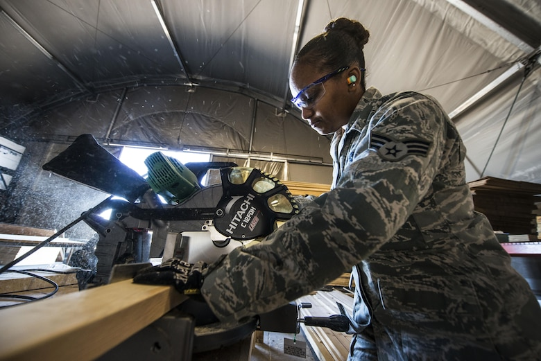 Senior Airman Marita McCoy uses a saw to cut a piece of wood Dec. 3, 2013, at Transit Center at Manas, Kyrgyzstan. McCoy used the wood to build the foundation of a scale to weigh cargo. McCoy is an inbound specialist with the 376th Expeditionary Logistics Readiness Squadron. (U.S. Air Force photo/Senior Airman George Goslin)
