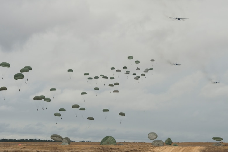 Army paratroopers float to the ground after successfully jumping from a C-130 Hercules Dec. 7, 2013, in support of Operation Toy Drop at Fort Bragg, N.C. The 16th Annual Randy Oler Operation Toy Drop, hosted by the U.S. Army Civil Affairs and Psychological Operations Command (Airborne), is the largest combined airborne operation in the world. During the event, Fort Bragg's paratroopers and allied jumpmasters donate toys to be distributed to children's homes and social service agencies across the local community. (U.S. Air Force photo/Airman 1st Class Logan Brandt)