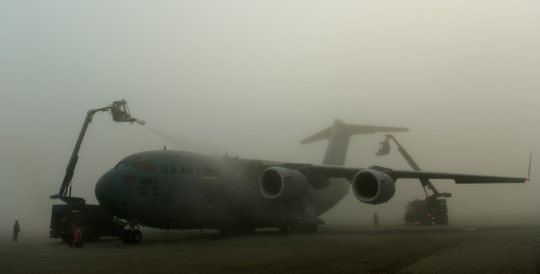 A C-17 Globemaster III is de-iced Dec. 11, 2013, by members of the 315th Aircraft Maintenance Squadron and the 446th Aircraft Maintenance Squadron on the flightline at Spangdahlem Air Base, Germany. De-icing is performed an hour before an aircraft's departure. The 315th AMXS is based at Charleston Air Force Base, S.C., and the 446th AMXS is from McChord Air Force Base, Wash. (U.S. Air Force photo/Senior Airman Rusty Frank)