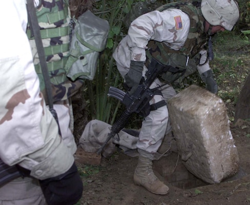 A member of 1st Brigade Combat Team lifts a Styrofoam lid covering the hole where former Iraqi dictator Saddam Hussein was discovered hiding Dec.13 in the village of Ad Dawr. Photo by Staff Sgt. David Bennett, USA