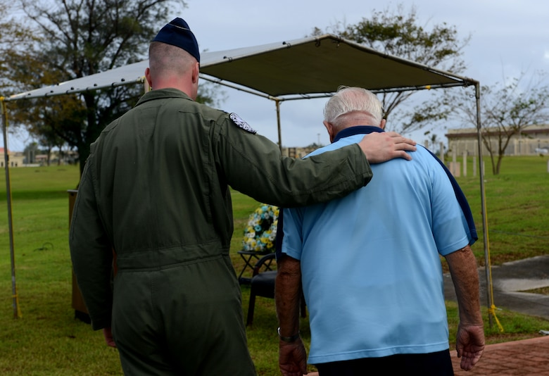 """Capt. Andrew Johnson leads retired Lt. Col. Charles """"Chuck"""" McManus to his seat prior to the Linebacker II ceremony Dec. 13, 2013, on Andersen Air Force Base, Guam. McMamus was a B-52 Stratofortess navigator during Operation Linebacker II, which took place in North Vietnam in December 1972. (U.S. Air Force photo by Airman 1st Class Emily A. Bradley/Released)"""