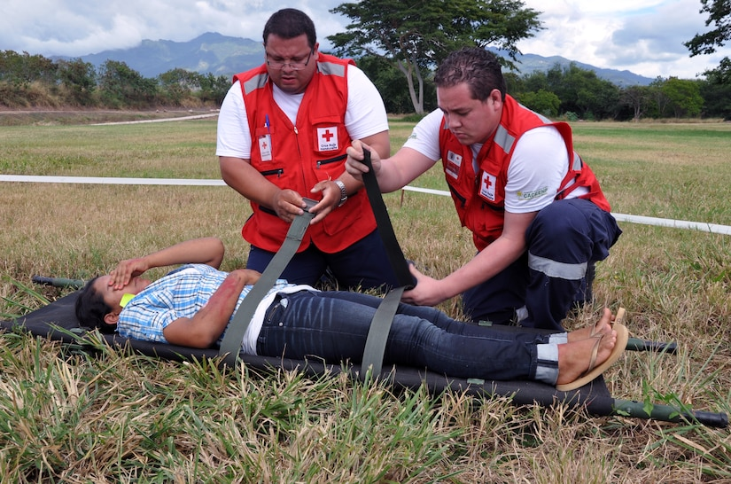 """Members of the Honduras Red Cross participate in a disaster response exercise as part of an American Academy of Pediatric Disaster """"Train the Trainer"""" course at Soto Cano Air Base, Honduras, Dec. 13, 2013. The three-day course provided training to members of the Honduran Academy of Pediatrics, the Honduran Red Cross, Honduran first responders, and members of the Permanent Contingency Commission of Honduras (COPECO) in the planning for and care of pediatric populations post-disaster. (U.S. Air Force photo by Capt. Zach Anderson)"""