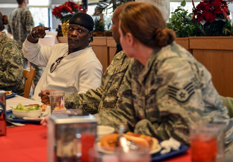 World Wresting Entertainment superstar, R-Truth, chats with Airmen during lunch at the McChord Field dining facility, Dec. 11, 2013, at Joint Base Lewis-McChord, Wash. WWE superstars and divas toured JBLM meeting and greeting service members prior to putting on a show at a McChord Field hangar later in the evening. (U.S. Air Force photo/Staff Sgt. Jason Truskowski)