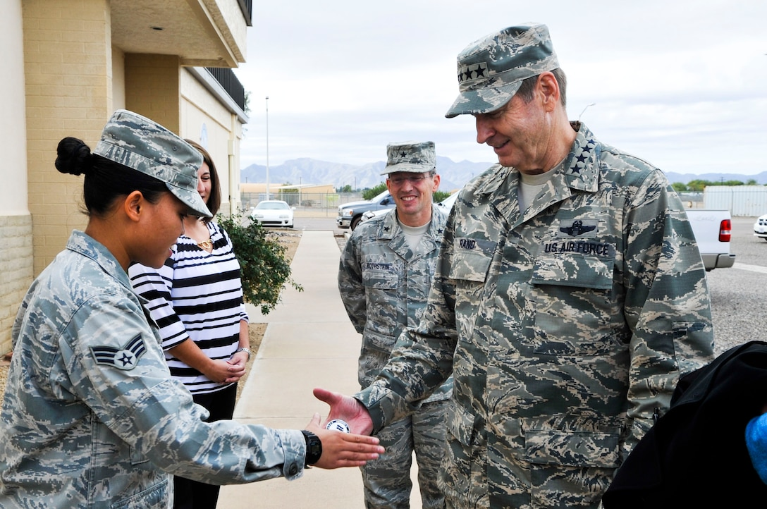 Gen. Robin Rand, Air Education and Training Command commander, presents a coin to Senior Airman Leonila Celestino, 607th Air Control Squadron knowledge operations management journeyman, Dec. 4 outside the 607th ACS building. Rand, a former wing commander at Luke, visited the base to talk to Airmen about his priorities and vision for AETC. (U.S. Air Force photo/Senior Airman David Owsianka)