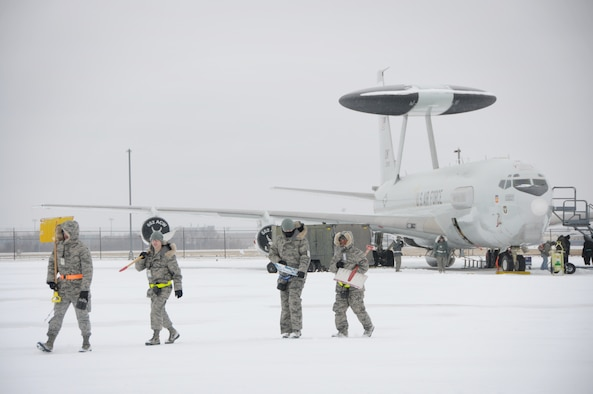 Maintenance Airmen head to another E-3 Sentry after shoveling snow around the aircraft on the flight line at Tinker Air Force Base on Dec. 6. Despite the freezing temperatures and snow that have blanketed the flight line, maintainers continue to service the Airborne Warning and Control System aircraft.  (Air Force photo by Staff Sgt. Caleb Wanzer)
