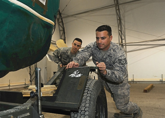 Senior Airman Barrington and Staff Sgt. William Medeiros both from the 386th Expeditionary Aircraft Maintenance Squadron, prepares a spare engine for a C-130 J, undisclosed location Southwest Asia. The Medeiros brothers deployed out of the 143rd Airlift Wing Rhode Island Air National Guard, Quonset Point Air National Guard Station and are natives of Rhode Island. (U.S. Air Force photo by Senior Airman Desiree W. Moye)