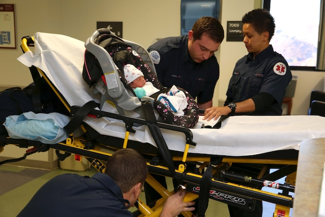 Emergency medical technicians began their process of relocating patients by securing an infant's car seat to a gurney for transportation. The Naval Hospital Camp Pendleton facility, built in 1969, was officially decommissioned, requiring patients to be relocated to Pendleton's, recently built, 500,000-square foot replacement hospital Dec. 14. The four-floor building cost $456 million and took more than three years to construct.