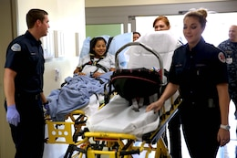 Emergency medical technicians escort Lance Cpl. Lucia Cabral and her newborn child to their room. The Naval Hospital Camp Pendleton facility, built in 1969, was officially decommissioned, requiring patients to be relocated to Pendleton's recently built, 500,000-square foot, replacement hospital Dec. 14. The four-floor building cost $456 million and took more than three years to construct. Cabral is a maintenance management specialist with1st Marine Logistics Group.